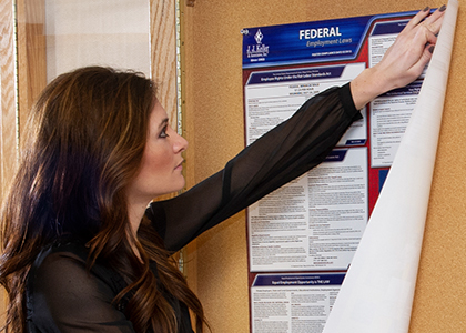 Employee hanging a labor law poster to make sure they are compliant with regulations